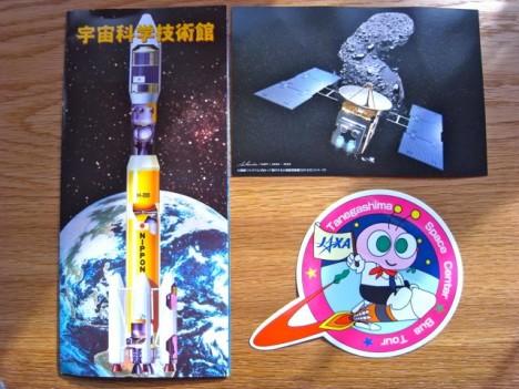 ▲左が宇宙科学技術館のパンフ、右上が「はやぶさ」カプセル展でもらった絵が葉書、右下がツアー参加者に配付されるステッカー